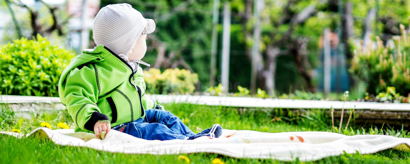 坐在春天的庭院里的男婴 库存图片