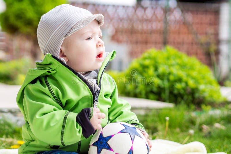 坐在春天的庭院里的男婴 库存照片