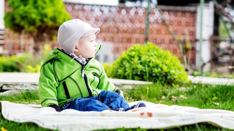 坐在春天的庭院里的男婴 免版税库存图片