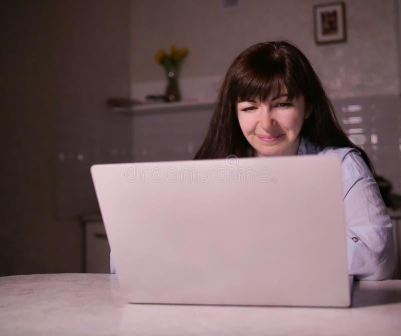 坐在晚上的逗人喜爱的微笑的年轻深色的妇女在她的有膝上型计算机的厨房里 库存图片