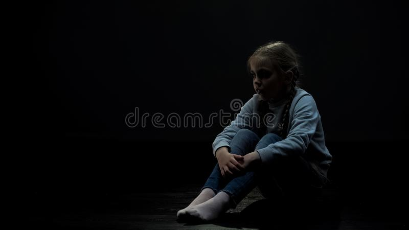 坐在暗室,单独恐惧和问题,孤儿孩子的翻倒女孩 免版税图库摄影