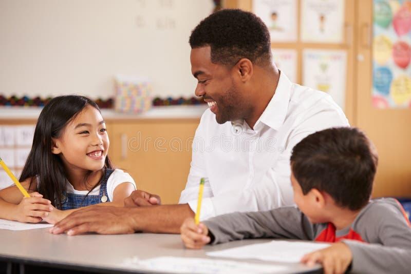 坐在有两个小学学生的书桌的老师 免版税库存图片