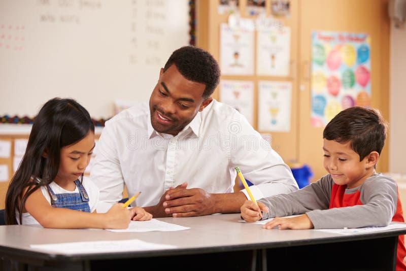 坐在有两个小学学生的书桌的老师 库存照片
