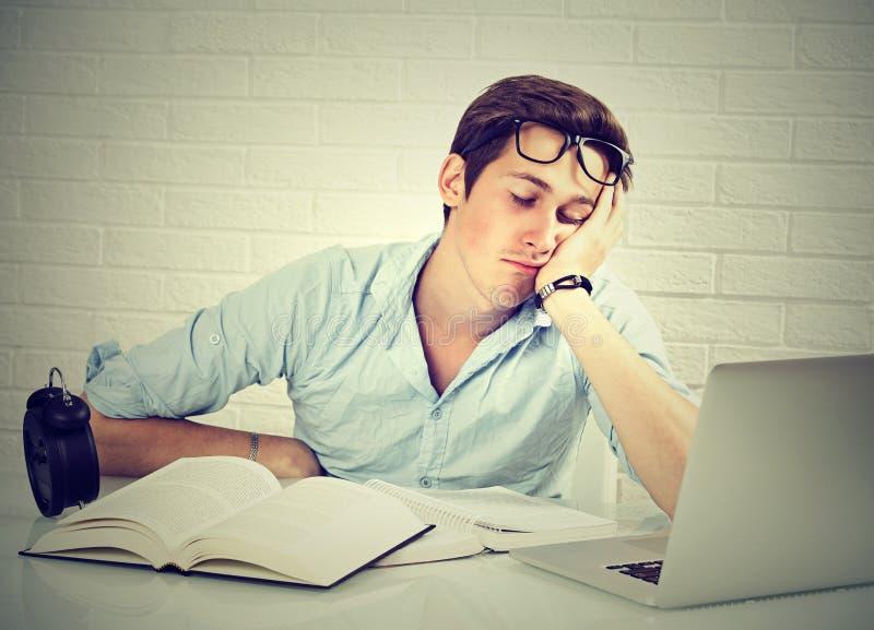 坐在有书的书桌的疲乏的困人在膝上型计算机前面 图库摄影