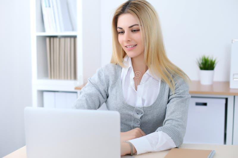 坐在有便携式计算机的办公室工作场所的年轻女商人或学生女孩 家庭企业概念 库存图片