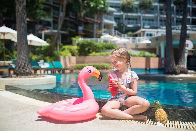 坐在有可膨胀的桃红色火鸟和饮用的新鲜的西瓜汁的游泳场附近的泳装的逗人喜爱的女孩 ?? 免版税库存照片