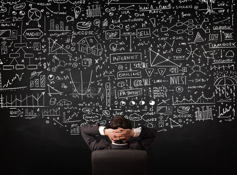 坐在有图的一个黑板前面的商人 免版税库存照片