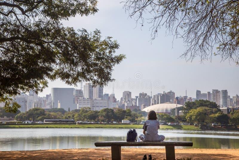 坐在有城市的湖前面的女孩作为backgroung 库存图片