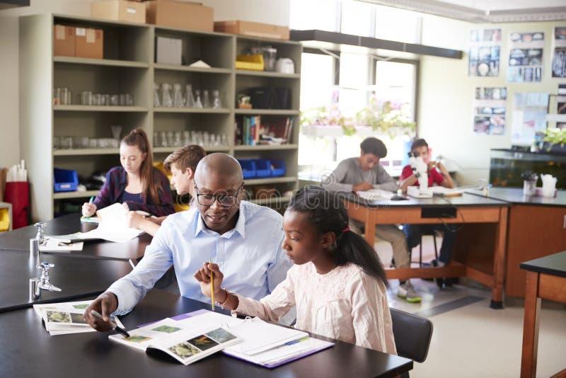 坐在有女学生的书桌的高中家庭教师生物课的 免版税库存照片