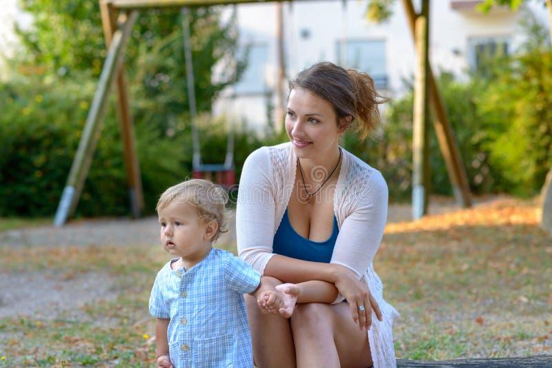 坐在有她的婴孩的一个操场的年轻母亲 图库摄影