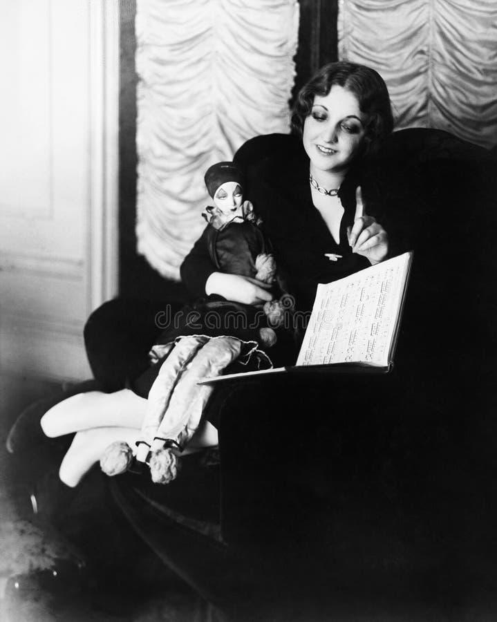 坐在有她的读书的木偶的一把扶手椅子的妇女(所有人被描述不更长生存,并且庄园不存在 一口 库存照片