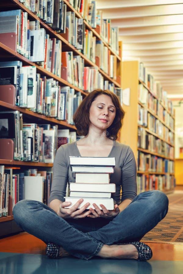 坐在有思考闭合的眼睛的图书馆里的疲乏的中年成熟女学生画象,睡觉 免版税库存照片