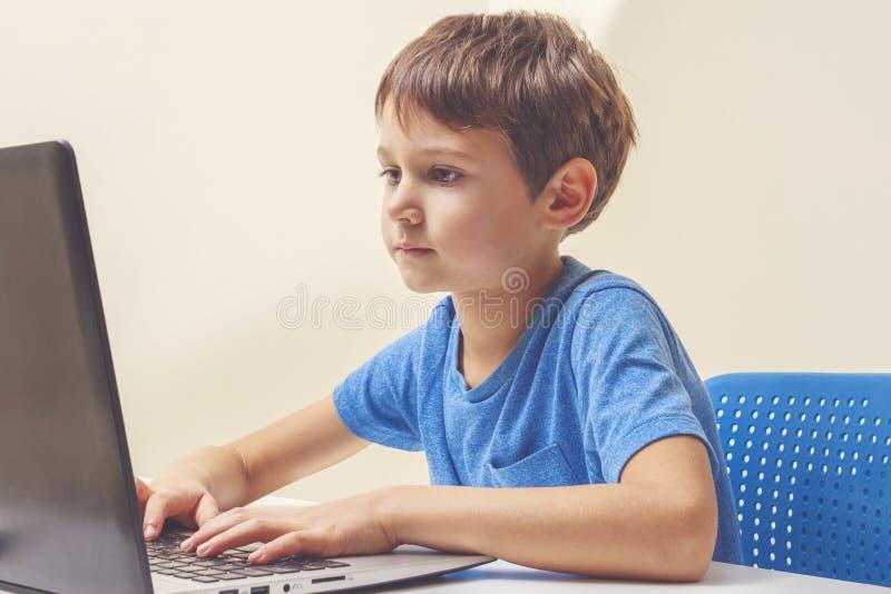 坐在有手提电脑的书桌和做家庭作业的被集中的男孩 免版税库存图片