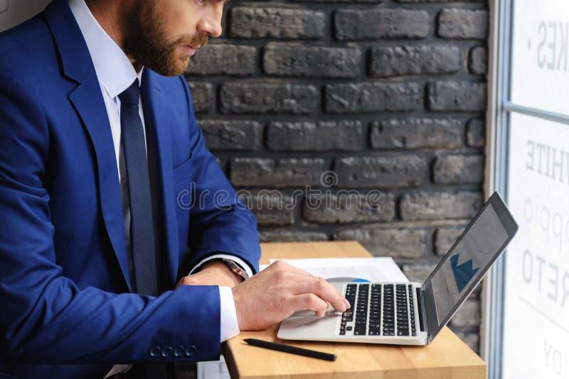 坐在有拷贝空间的笔记本前面的人 免版税库存照片