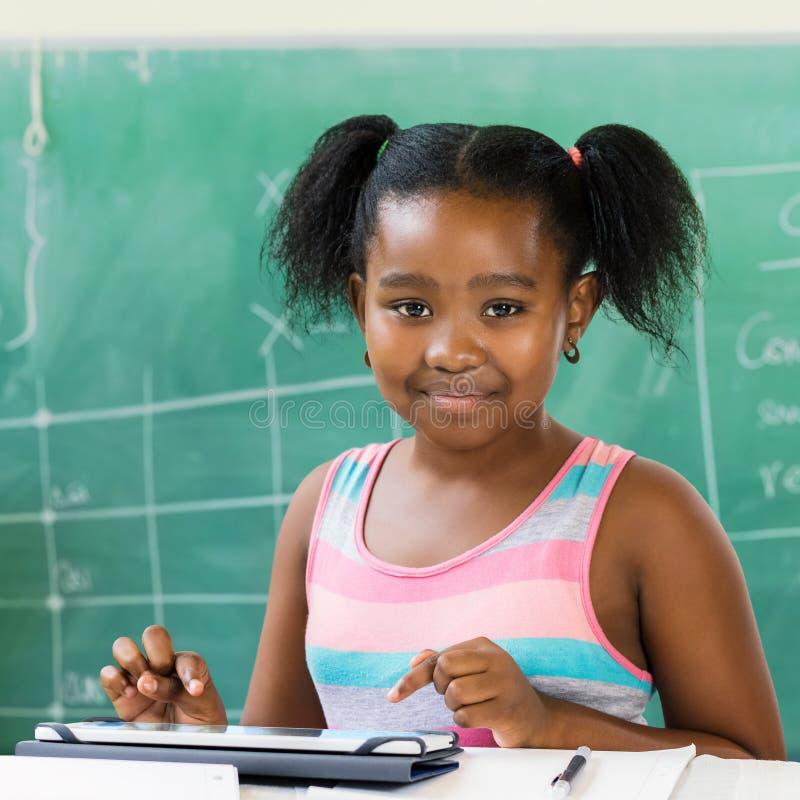 坐在有数字式片剂的书桌的小非洲学生在分类 库存照片