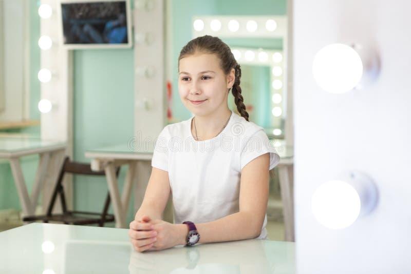 坐在有斑点的镜子前面的青少年的年龄女孩女演员轻在绿色屋子里 免版税库存图片