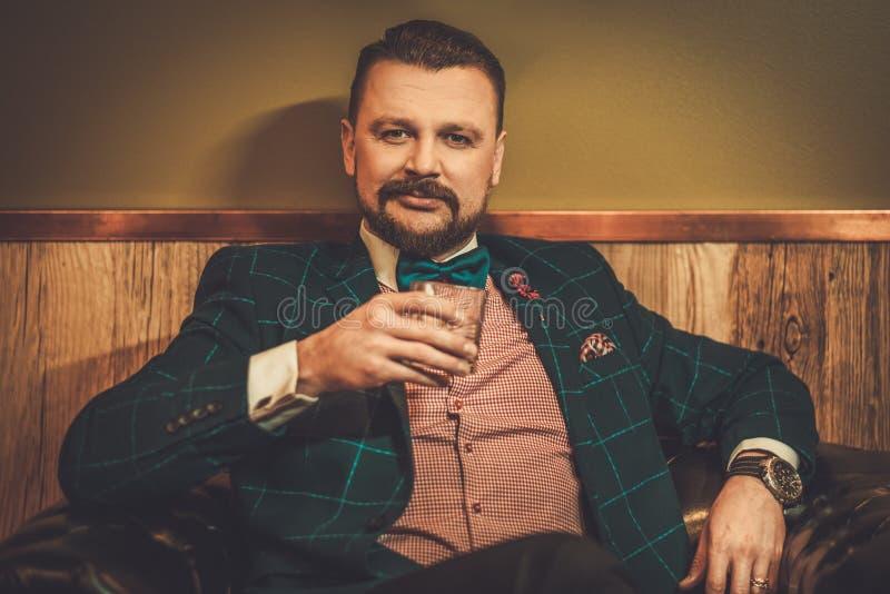 坐在有杯的舒适的皮椅的确信的古板的人在木内部的威士忌酒在理发店 免版税库存图片