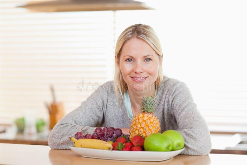 坐在有果子牌照的厨房里的妇女  免版税库存照片