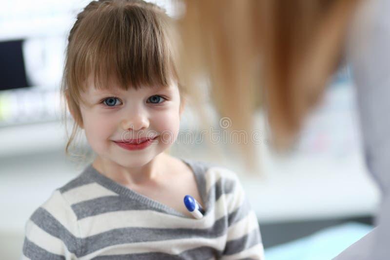 坐在有温度计的医生办公室的逗人喜爱的女孩画象 库存照片