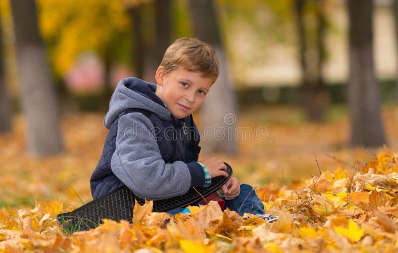 坐在有滑板的公园的微笑的年轻男孩 免版税库存照片