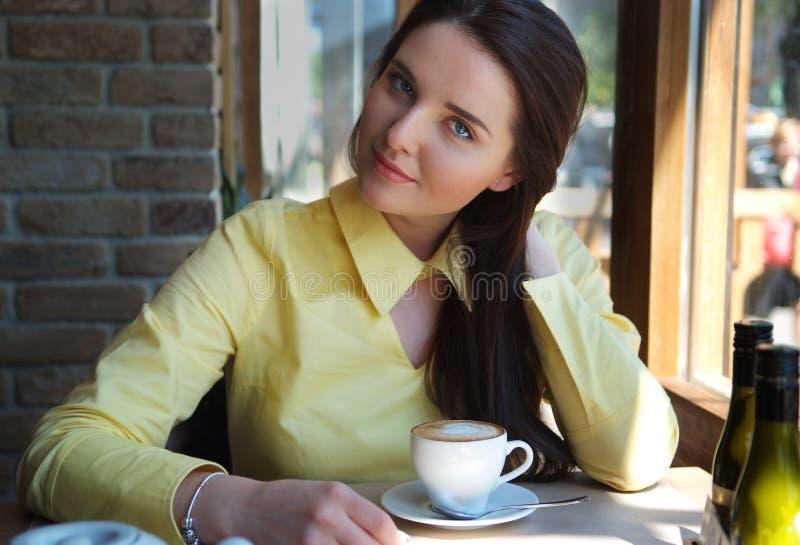 坐在有热奶咖啡的餐馆的微笑的美丽的少妇 免版税库存照片