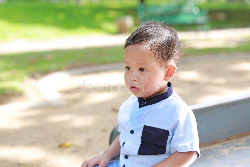 坐在有看的庭院的平安的亚裔男婴画象  免版税库存图片