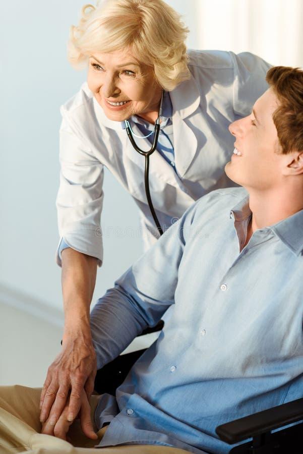 坐在有站立在他的医生的轮椅的微笑的年轻人握他的手 免版税库存图片