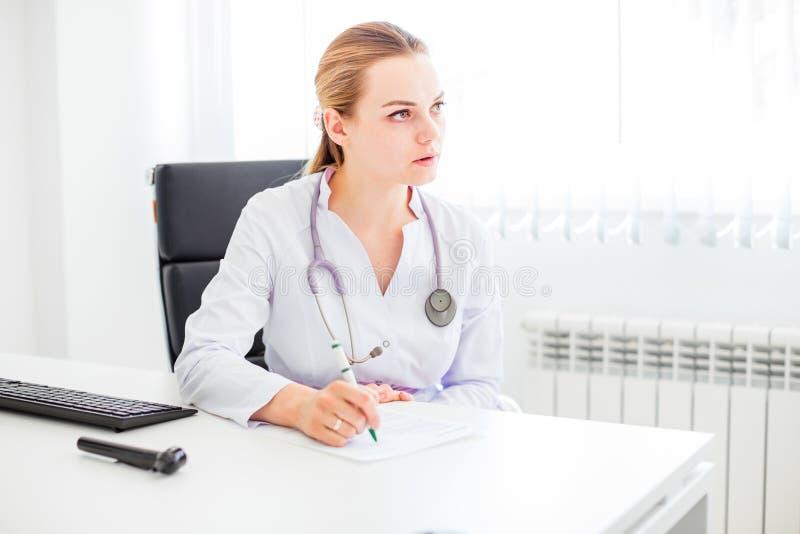 坐在有笔和听诊器的书桌的年轻微笑的女性白肤金发的医生 免版税库存照片