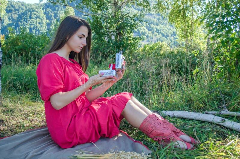 坐在有箱子的草甸的女孩 免版税库存图片