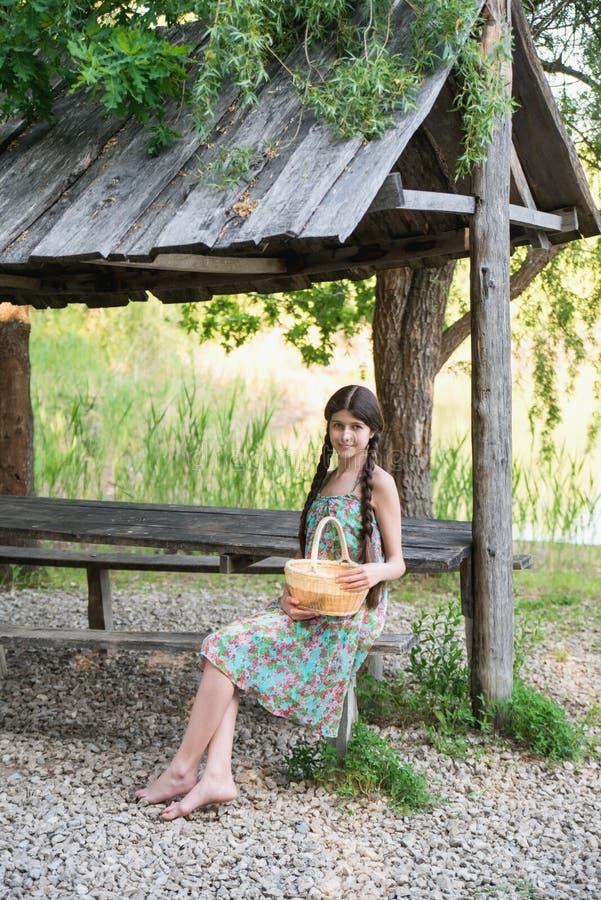 坐在有篮子的森林里的好女孩 库存照片