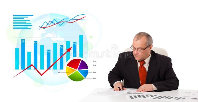 坐在有统计数据的服务台的生意人 库存图片