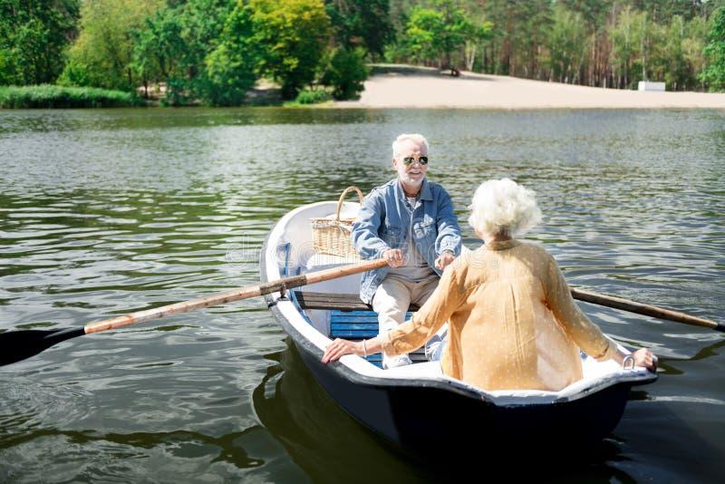 坐在有美丽的妻子的小船的有胡子的年长丈夫 库存照片