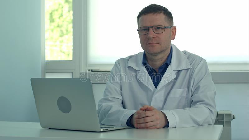 坐在有膝上型计算机的书桌和看照相机的成熟男性医生在他的诊所办公室 免版税库存照片