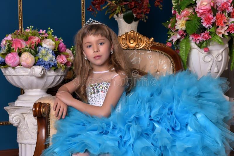 坐在有花的花瓶中的一件蓝色礼服的逗人喜爱的小女孩 库存照片