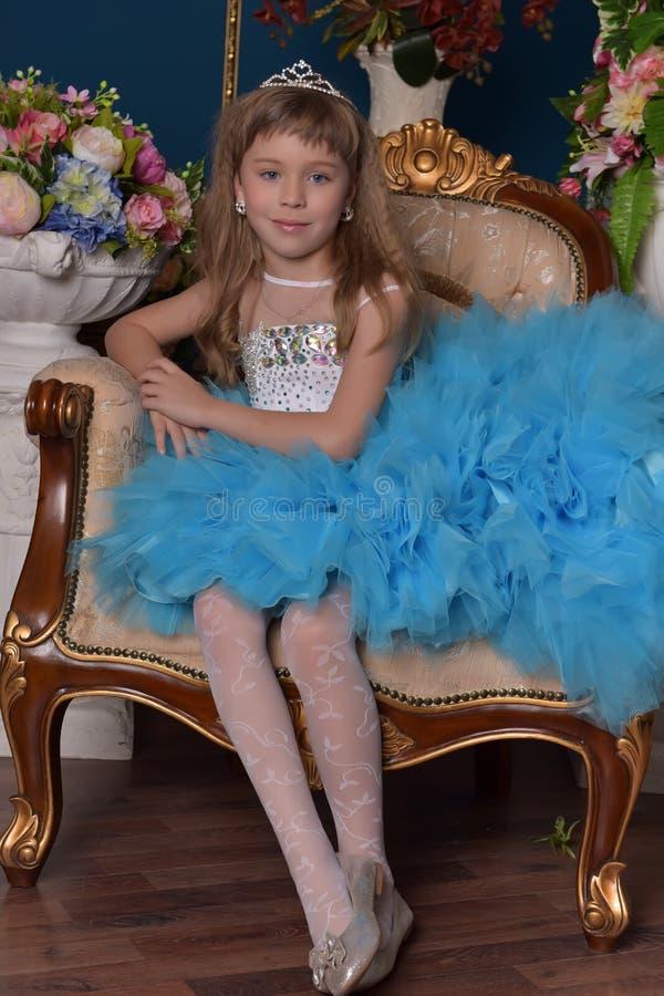 坐在有花的花瓶中的一件蓝色礼服的逗人喜爱的小女孩 图库摄影