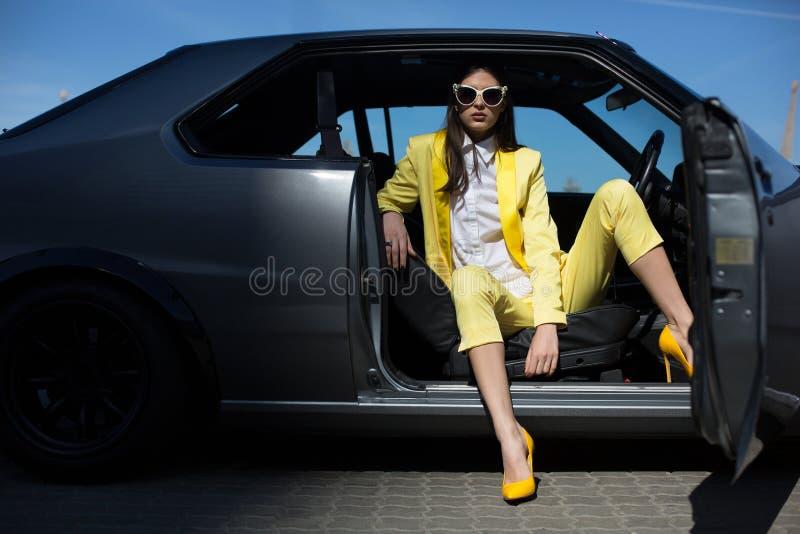 坐在有被打开的门的汽车的时髦的夫人 塑造驾驶在衣服的女孩一辆汽车 免版税库存照片