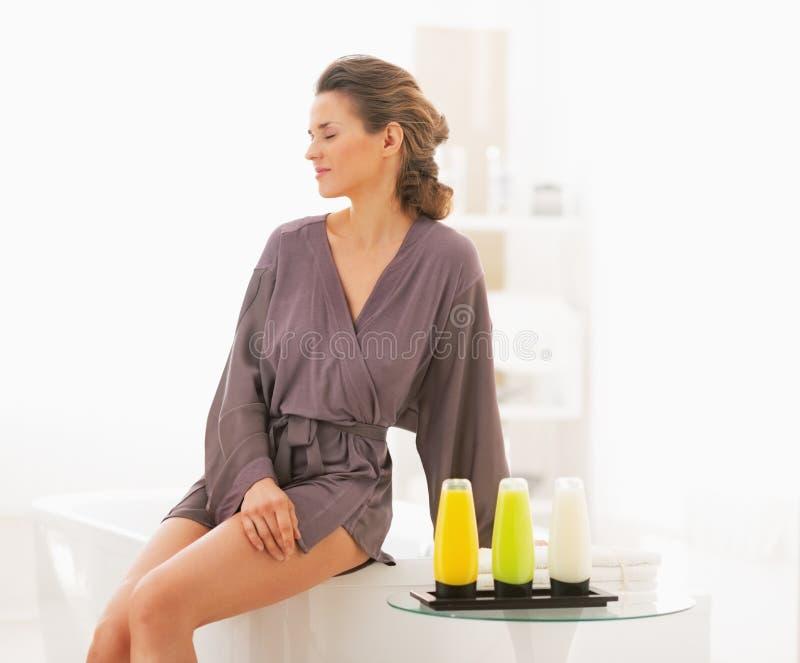 坐在有浴化妆用品的卫生间里的少妇 库存图片