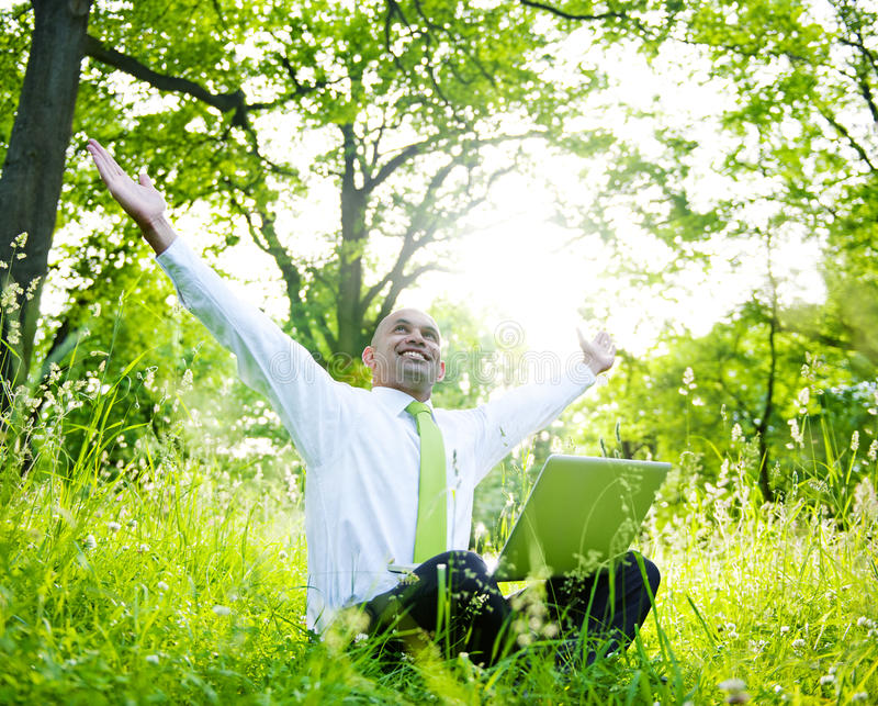 坐在有他的膝上型计算机的一个森林里的商人 库存照片