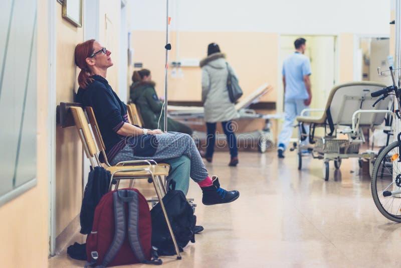坐在有iv的医院病房走廊候诊室的患者 免版税库存图片
