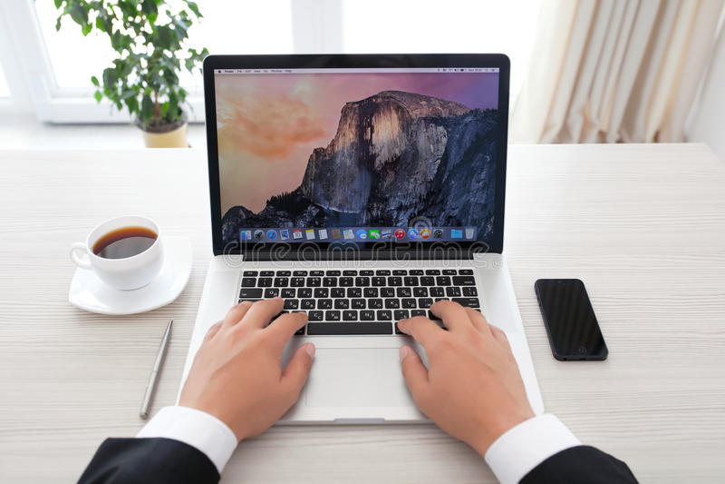 坐在有OSX的优胜美地MacBook赞成视网膜的商人 库存图片