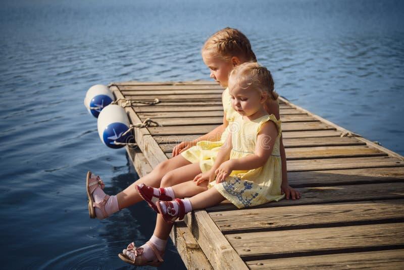 坐在木码头的黄色礼服的两个妹近 免版税图库摄影