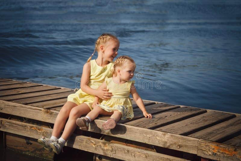 坐在木码头的黄色礼服的两个妹近 免版税库存图片