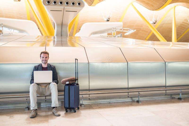 坐在机场的年轻可爱的人与lapto一起使用 库存图片