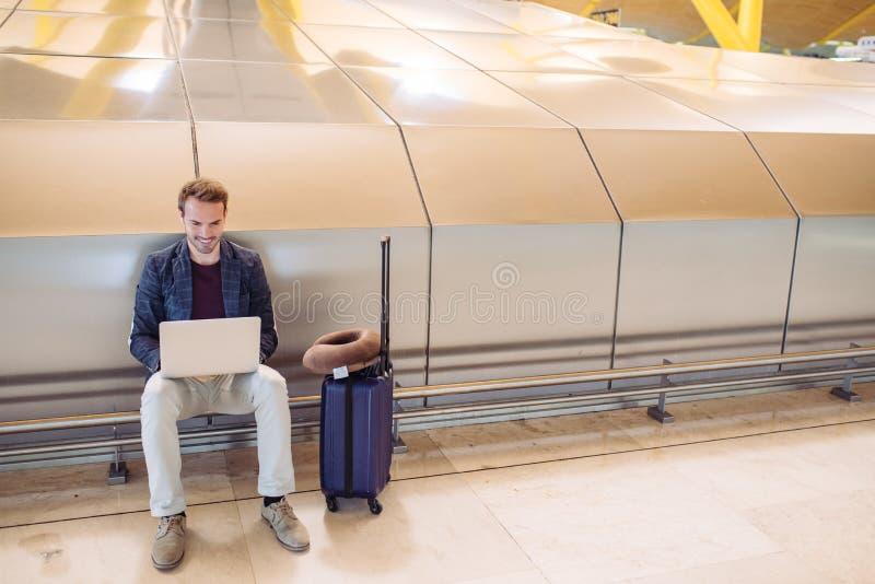 坐在机场的年轻可爱的人与lapto一起使用 免版税图库摄影