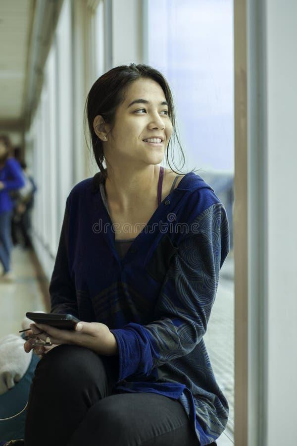 坐在机场等待的飞行的青少年的女孩 免版税库存照片