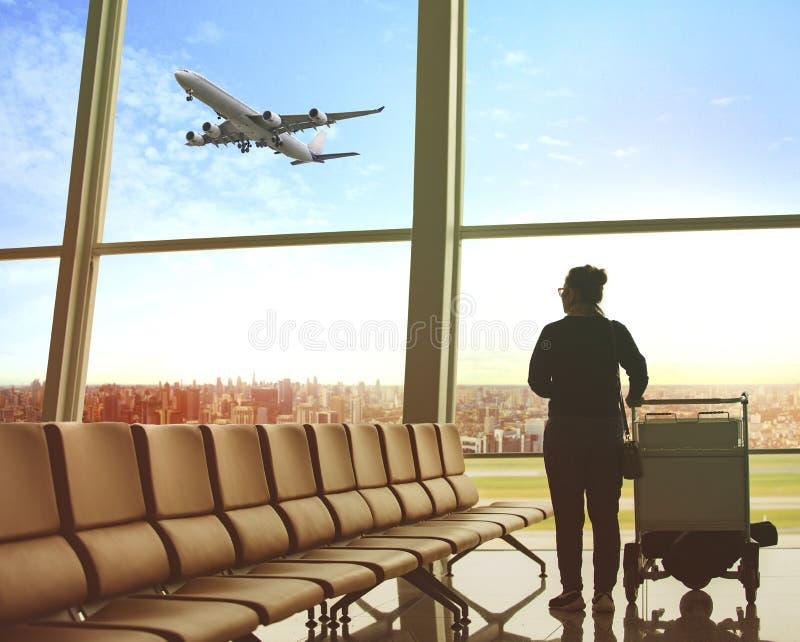 坐在机场终端和客机飞行的单身妇女 免版税库存照片