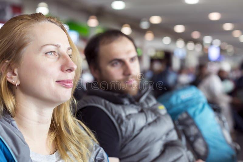 坐在机场终端的男人和妇女 免版税图库摄影