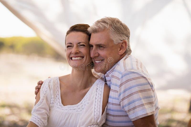 坐在村庄的愉快的夫妇 库存图片