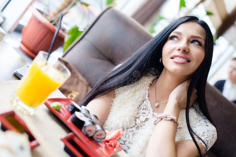 坐在查寻寿司餐厅或咖啡店美丽的性感的深色的女孩的少妇有乐趣愉快微笑& 免版税库存图片