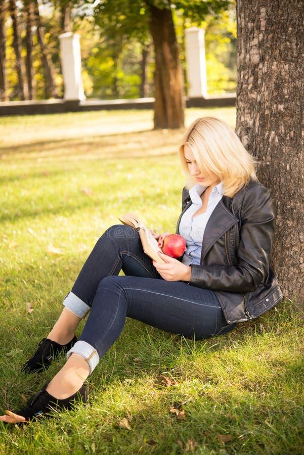坐在树下和读书的美丽的女孩 免版税库存照片